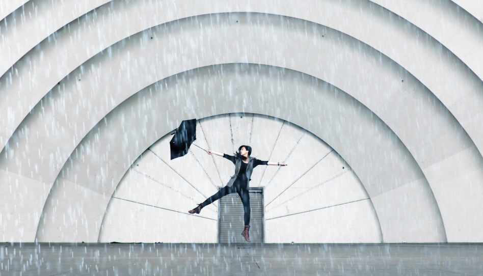 Frau tanzt voller Freude im Regen