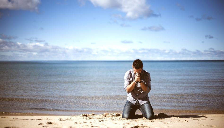 Mann kniet betend am Strand
